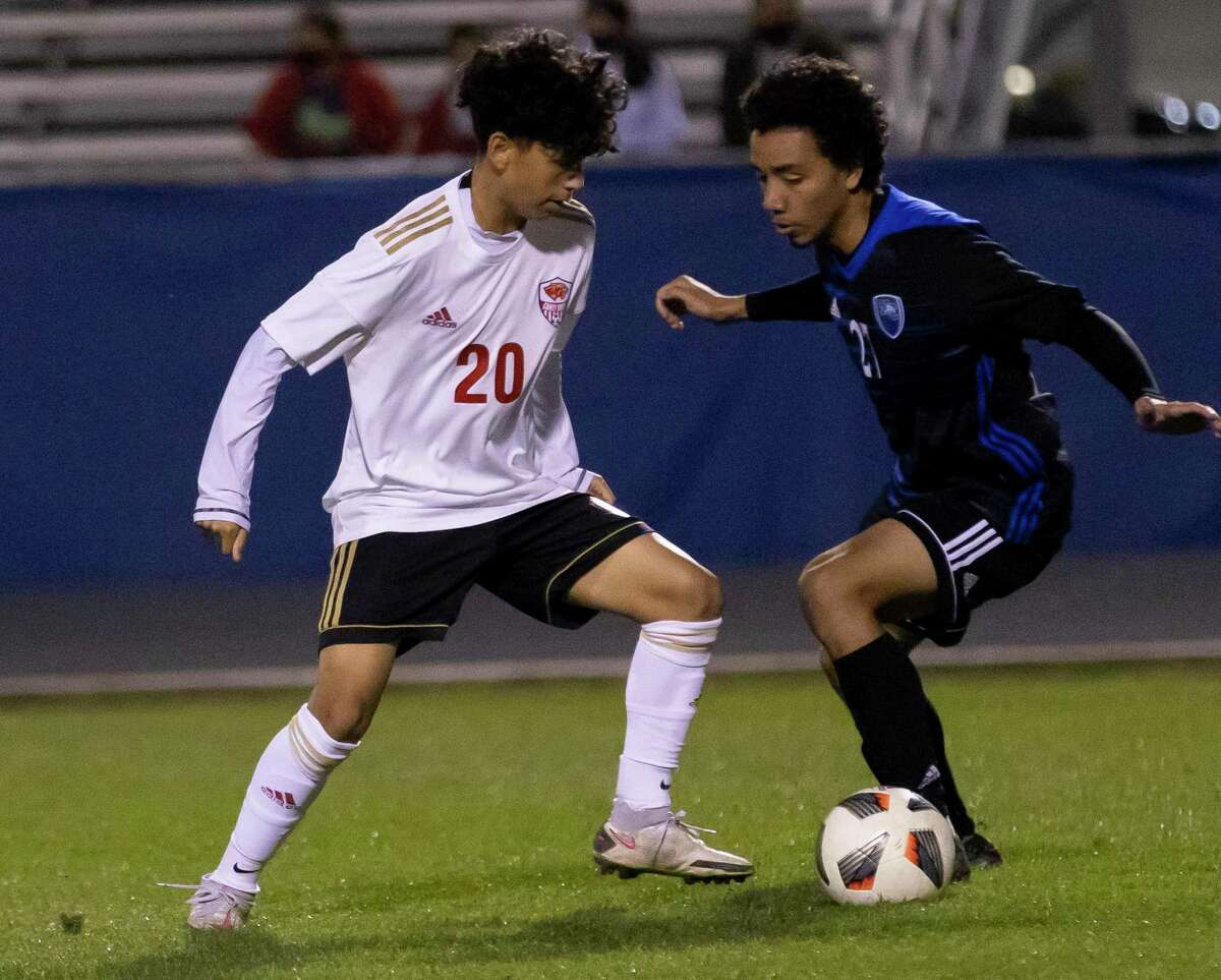 Caney Creek's Alexis Cruz (20) and New Caney's Ronny Del Cid fight for control of the ball during the first half of a District 20-5A boys soccer match at Don Ford Stadium, Tuesday, March 9, 2021, in New Caney.