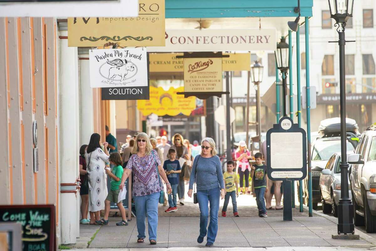 People walk past shops in the Strand on Tuesday, March 9, 2021, in Galveston. The island is preparing for the start of Spring Break next week.