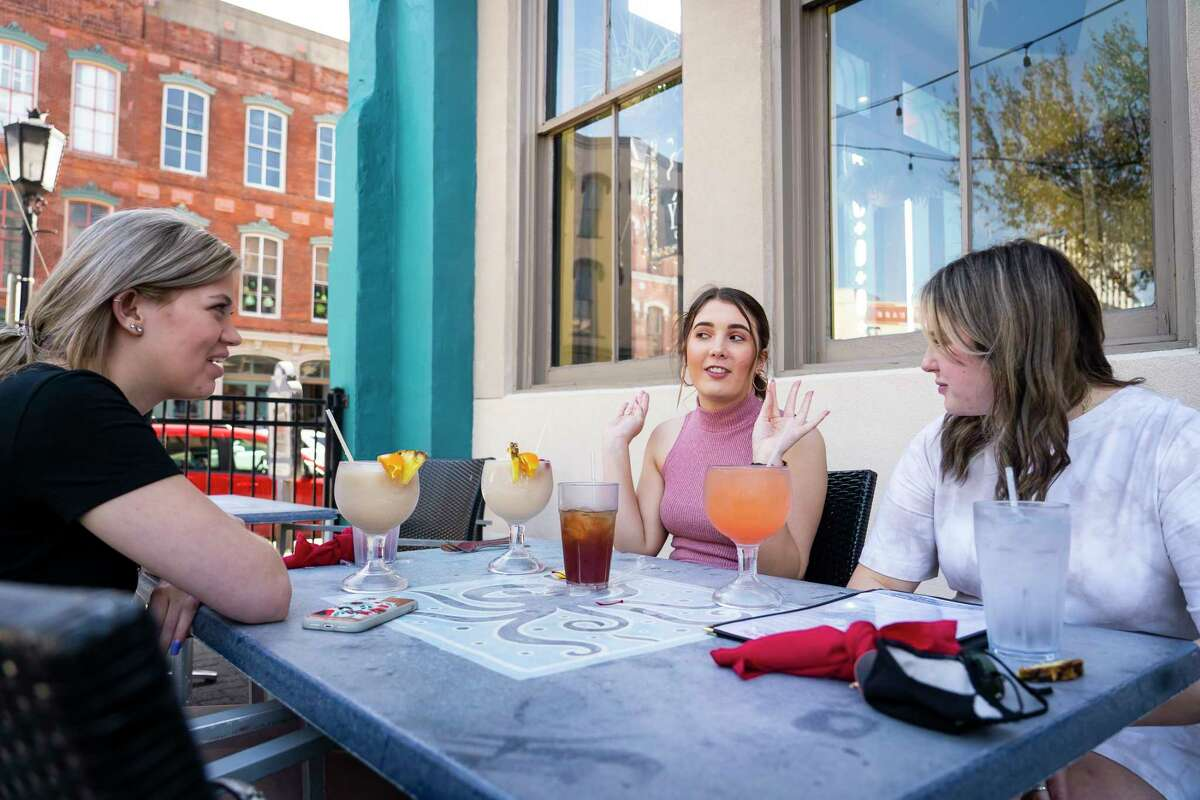 Friends Morgan Winger (left), Peyton Emory and Payton Turow talk talk as they eat lunch at Yaga's Cafe on Tuesday, March 9, 2021, in Galveston. The friends, all juniors in college, were spending a few days on Galveston Island enjoying their respective spring breaks.