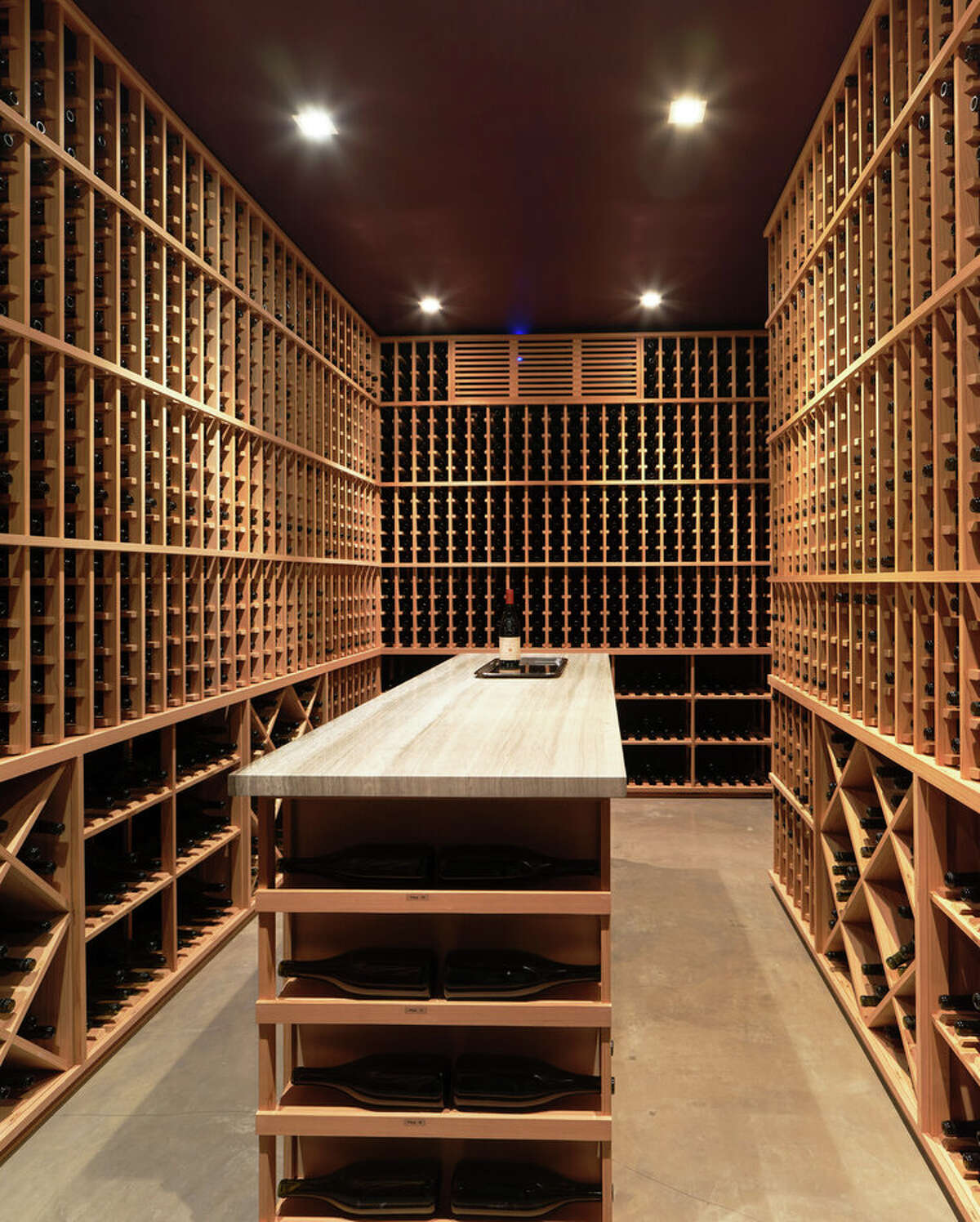 The aforementioned wine room is on the lowest level, which is accessed via a terraced entry that sits atop a two-car side-by-side garage. This floor also has a full bath and amedia room with 110-inch drop-down projection screen and surround sound.