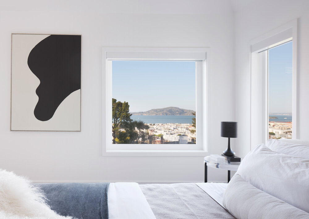 There are three bedrooms, two bathrooms and a laundry room on the upper level. The primary bedroom faces north to best take in the bay views. The other two bedrooms face south and overlook the pool below from a shared deck.