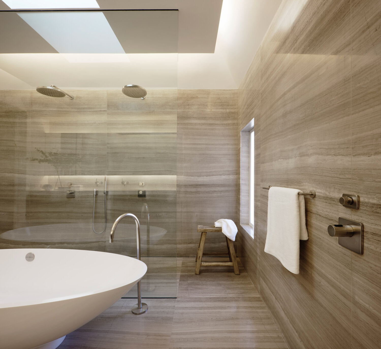The primary bathroom has dual shower heads, a soaker tub and is skylit from above.