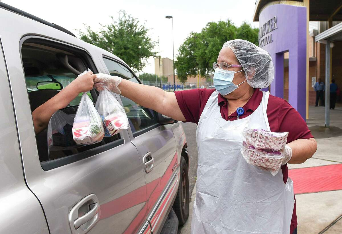 Cafeteria workers Edna Cassiano hands out breakfast and lunch packs to students on March 23, 2020 during the LISD Grab and Go meal program at J.Z. Leyendecker Elementary School.