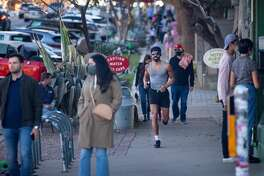 AUSTIN, TX - MARCH 03: Pedestrians walk down South Congress Ave. on March 3, 2021 in Austin, Texas. Gov. Greg Abbott announced today that the state will end its mask mandate and allow businesses to reopen at 100 percent capacity on March 10. (Photo by Montinique Monroe/Getty Images)