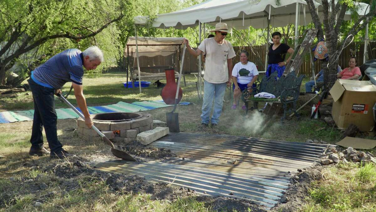 """Adán Medrano, left, seals the earth oven to prepare barbacoa in a scene from the documetary feature film, """"Truly Texas Mexican."""""""