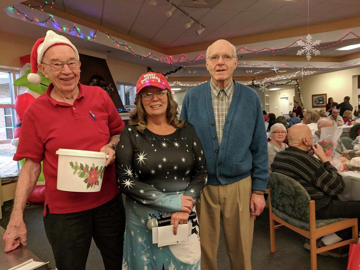 Midland Kiwanis volunteers Jim Ward and Ed Younkers pose with Dawn Powell, director of the Sanford Senior Center, as about 115 Sanford seniors recently enjoy a Christmas party at the Senior Services Midland Council on Aging in 2018. (Photo provided)