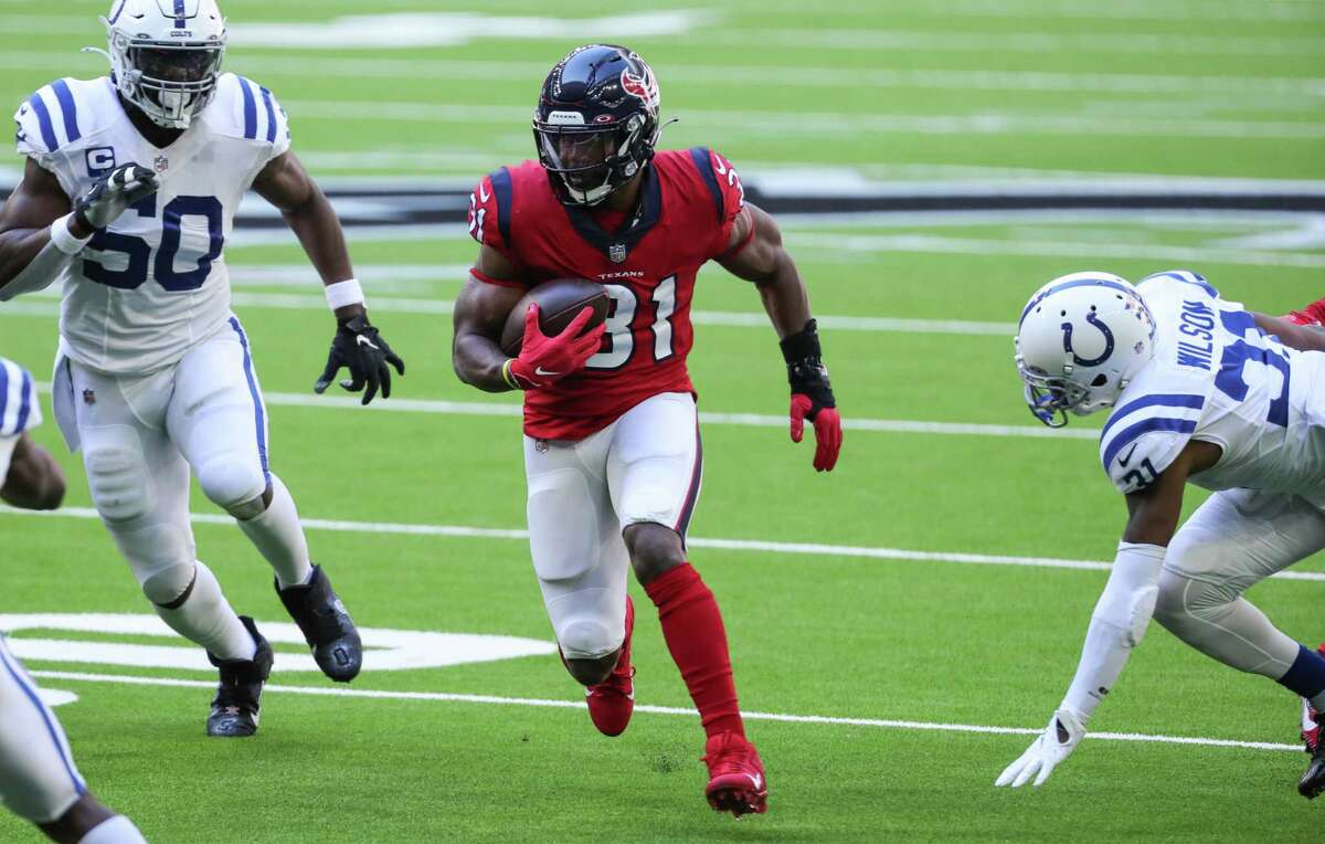 Houston Texans running back David Johnson (31) runs the ball between Indianapolis Colts defensive end Justin Houston (50) and defensive back Tavon Wilson (31) during the first half of an NFL football game at NRG Stadium on Sunday, Dec. 6, 2020, in Houston.