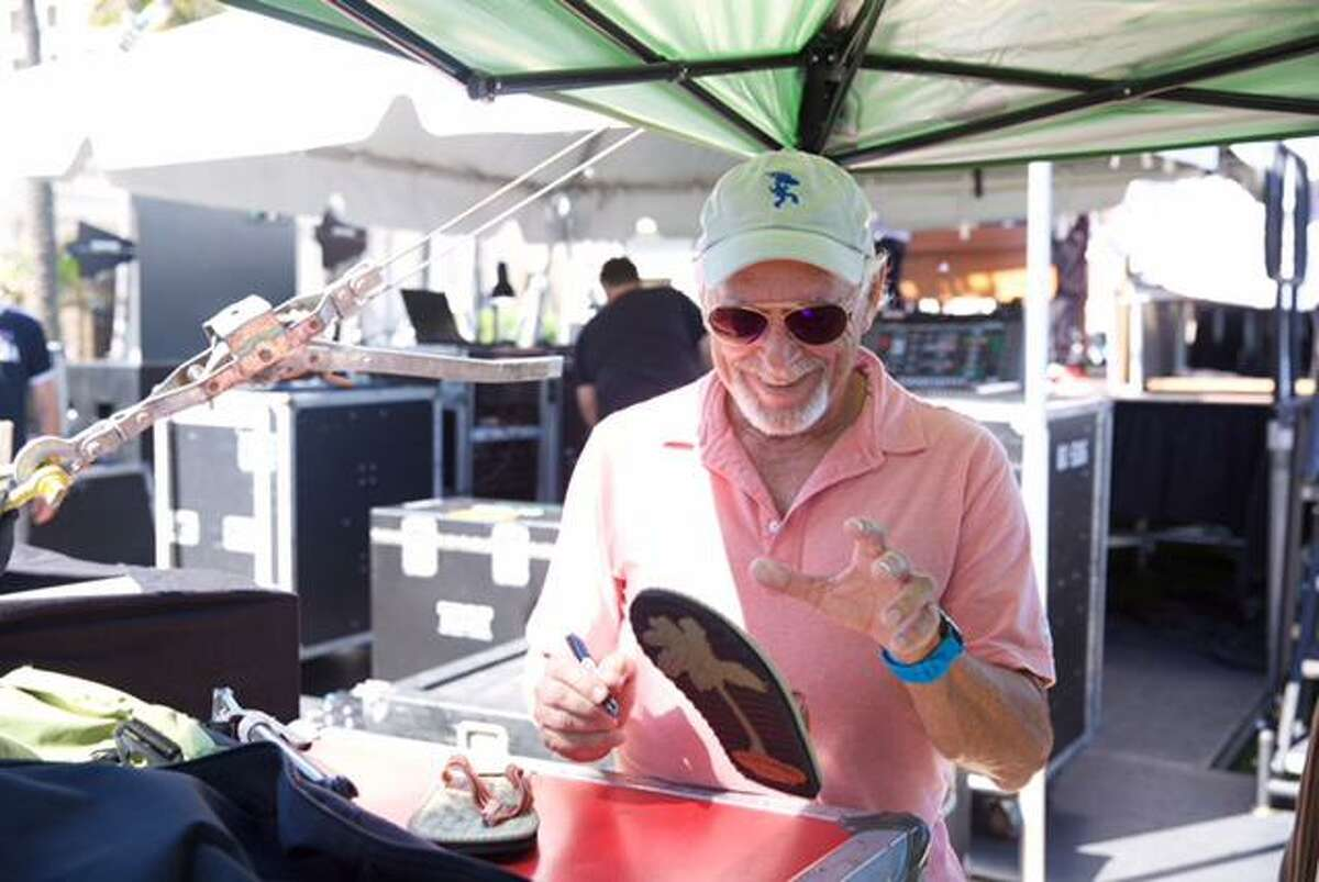 Jimmy Buffett is pictured signing a flip flop for a Parrothead fundraiser. There are more than 200 Parrothead clubs across the world.