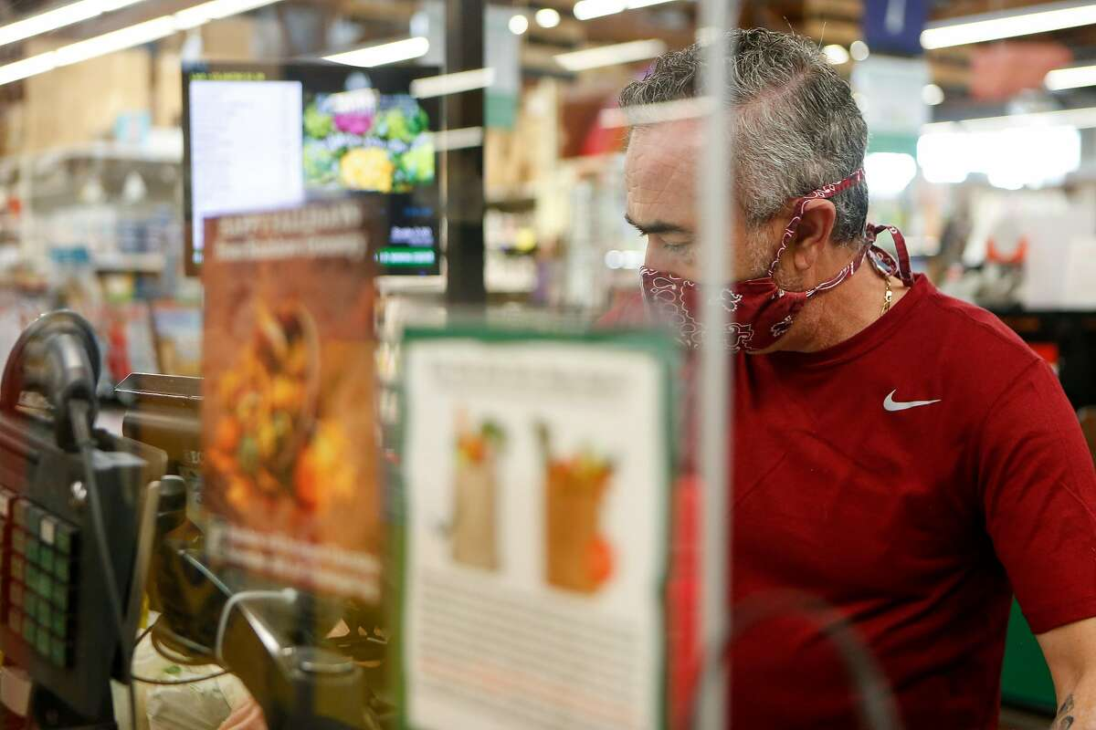 Juan Salazar checks out a customer from behind plexiglass at Rainbow Grocery in November in San Francisco.