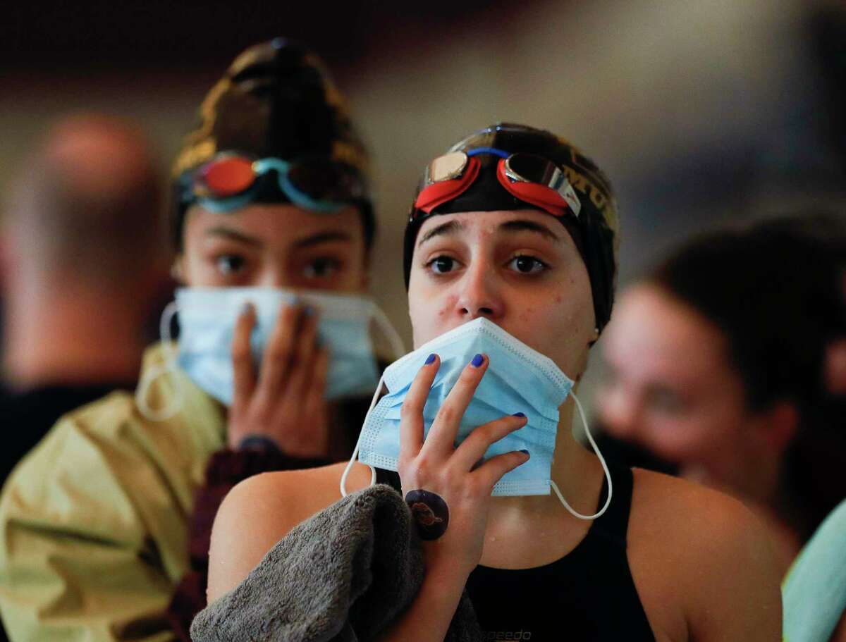 Magnolia West swimmers hold up their face mask after competing in the girls 200-yard medley relay during the District 21-5A Swimming and Diving Championships at the Conroe ISD Natatorium on Jan. 29 in Shenandoah. As of Wednesday, four public districts in Montgomery County had announced they would be continuing to mandate masks.