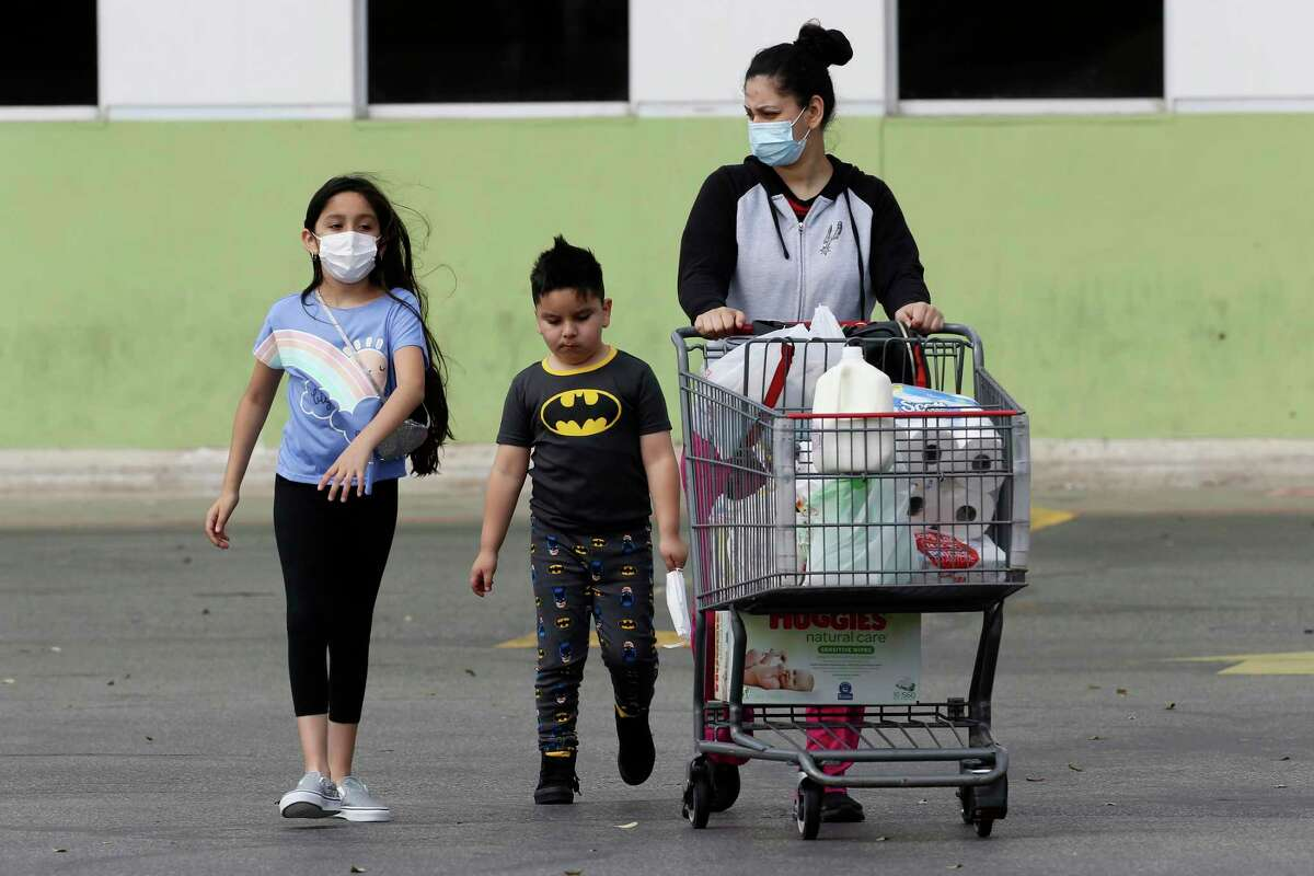 A family leaves after shopping the H-E-B on W.W. White Road, Wednesday, March 10, 2021. It is the first day that Gov. Greg Abbott's rescinding the mask mandate and returning 100-percent capacity for restaurants.