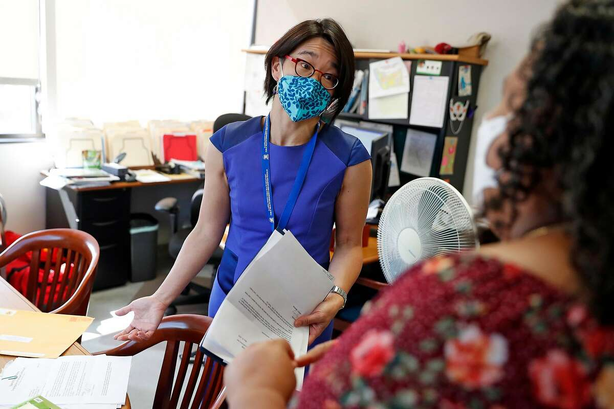 Dr. Erica Pan, state epidemiologist and former Alameda County health officer, chats with an administrative assistant in her Oakland office last year.
