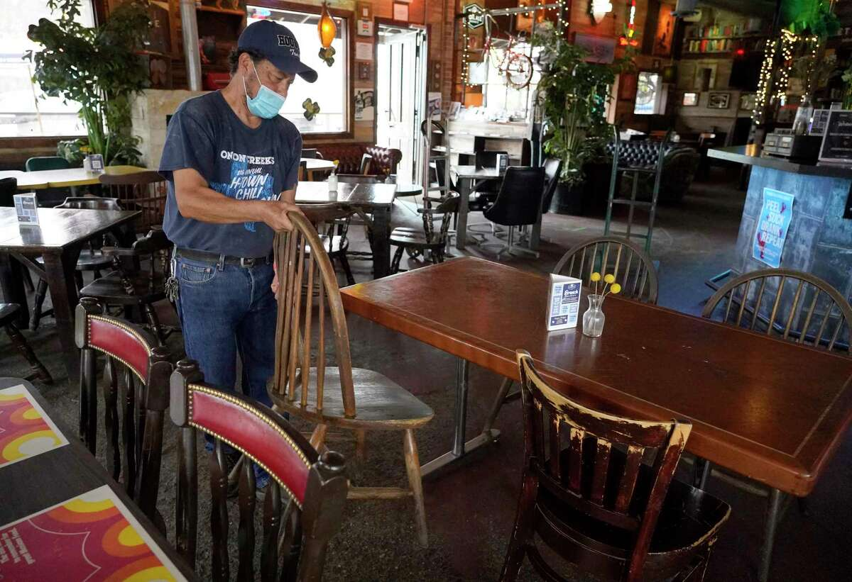 Employee Moses Garcia adds more seating to open the dining room for 100 percent capacity at Cedar Creek Bar & Grill, 1034 W. 20th St., Wednesday, March 10, 2021 in Houston.