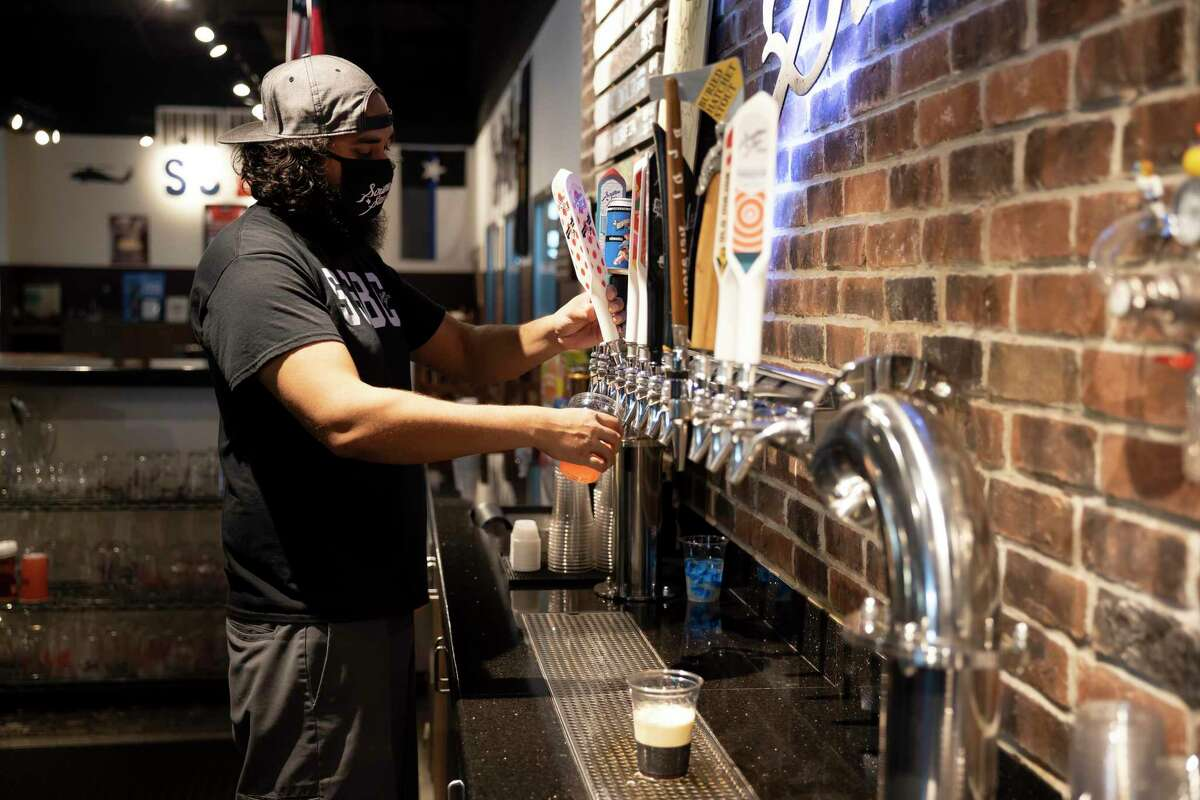 Harpreet Rall, bartender at Southern Star, fills a cup of beer during Wine Fest in Conroe, Saturday, Nov. 7, 2020. The annual wine fest event shifted to a COVID-19 format where small groups of people get a passport and a map to visit multiple breweries and wineries around Lake Conroe.