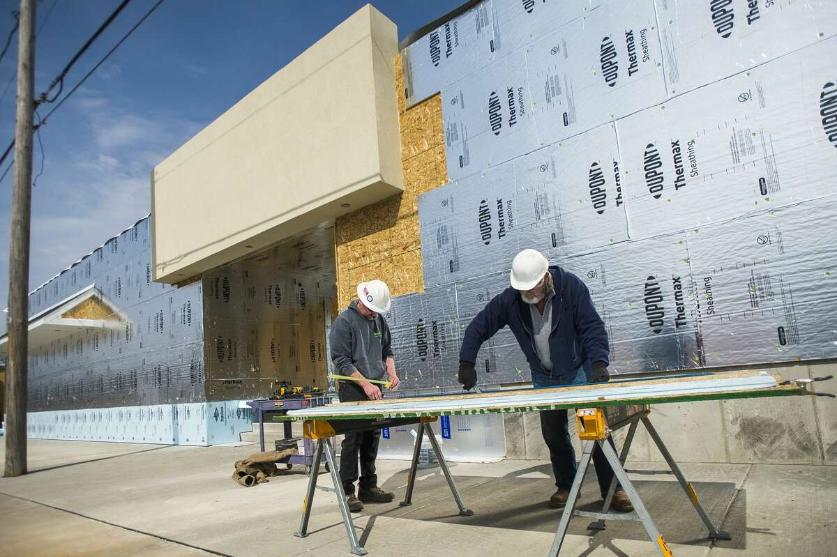 Brandon LeVasseur, left, and Walt Wright, right, work to install insulation at Sanford Hardware as construction continues Wednesday, March 10, 2021 in downtown Sanford. (Katy Kildee/kkildee@mdn.net)