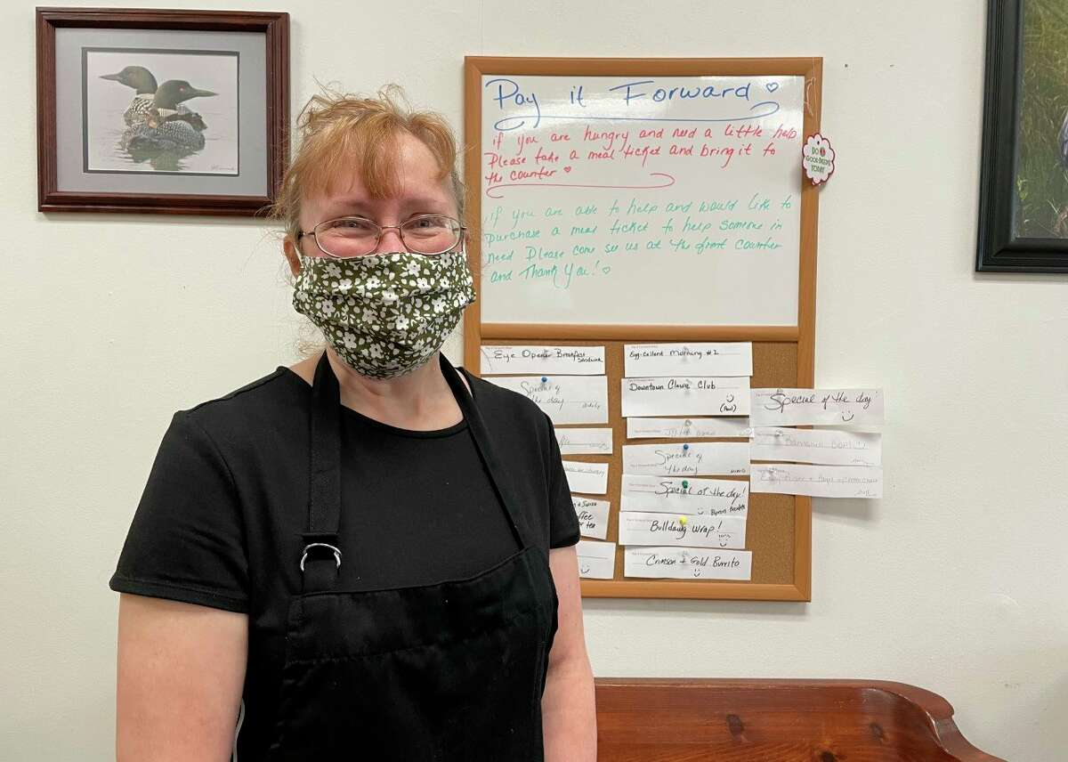 Paula Beilfuss, owner of Three Girls Bakery, dons a big smile -- behind her mask -- as she poses in front of her newly-created Pay It Forward board. The purpose is two-fold: if you are hungry and in need of a meal, stop in to the Big Rapids bakery, grab a ticket and enjoy a meal. If you are able to help out someone in need, you can purchase a meal ticket -- there's several choices to pick from -- and place it on the board. Three Girls Bakery is located at 106 N. Michigan Ave. in downtown Big Rapids. (Pioneer photo/Bradley Massman)