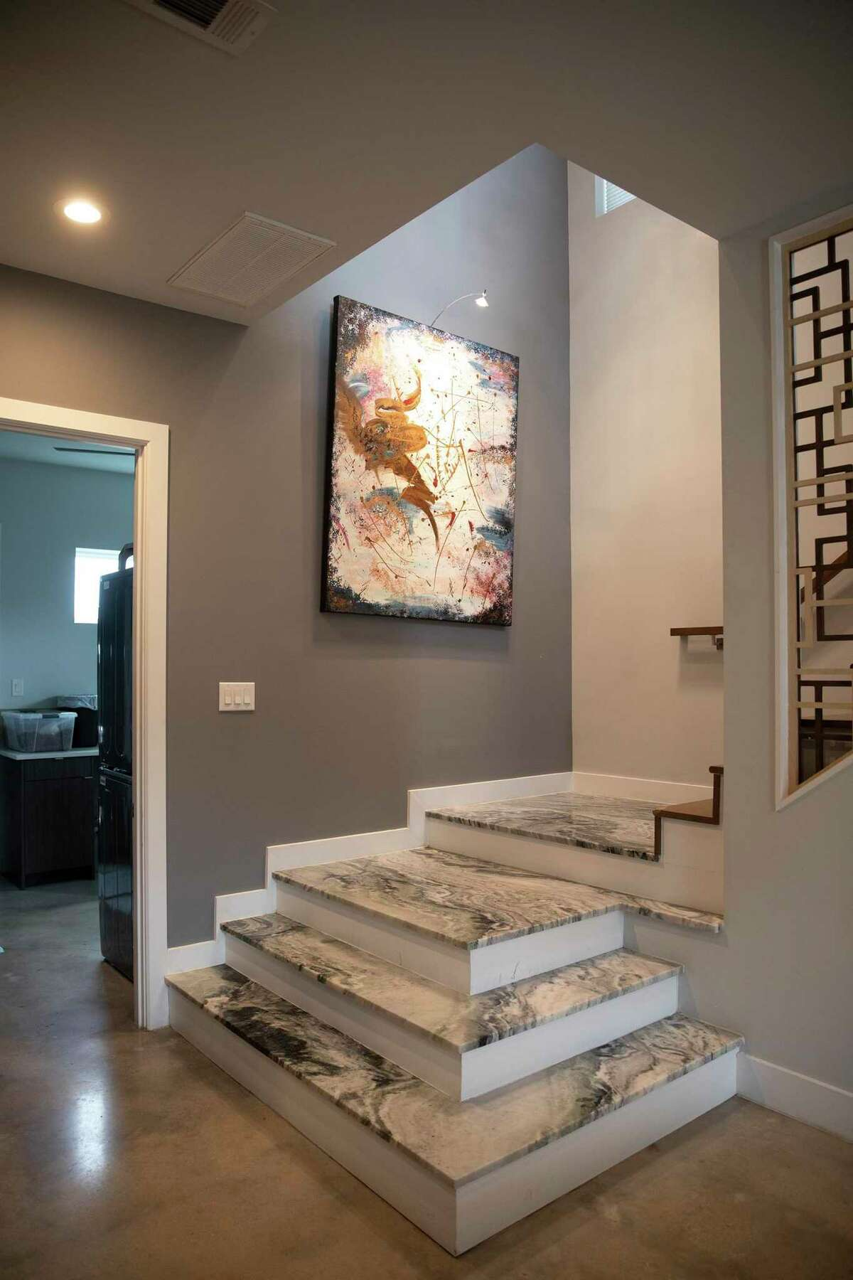 Another one of the custom touches was to have the plain white marble originally planned for the first four steps that spill out into the ground floor living area made with green and white marble instead.