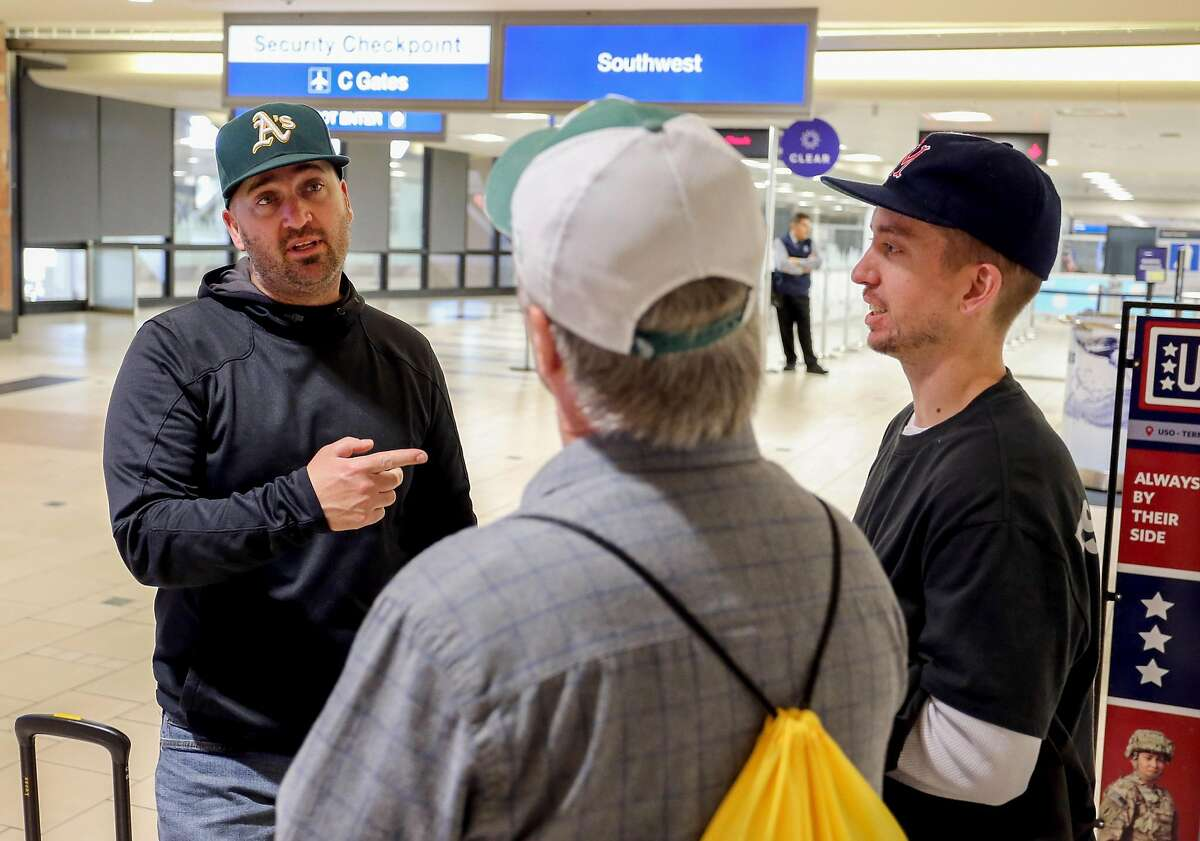 Vallejo residents and Oakland A's baseball fans Jesse Peterson talks to his dad Scott (middle) and brother Andrew (right) while waiting to go through the Security Checkpoint at Phoenix Sky Harbor International Airport Saturday, March 14, 2020, in Scottsdale, Arizona. The Peterson's were in Arizona for spring training games but failed to catch any games after they were cancelled, but the trio made best of the situation by playing golf and eating at some good local restaurants.