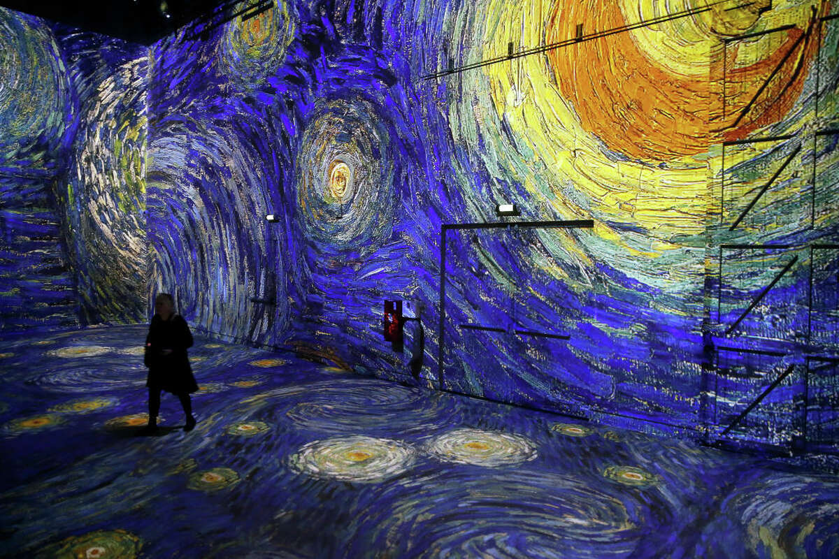 """PARIS, FRANCE - FEBRUARY 21: Visitors attend a press preview of the immersive exhibition """"Van Gogh, Starry Night"""" (Van Gogh, La nuit etoilee) devoted to painter Vincent Van Gogh by multimedia artist Gianfranco Iannuzzi at the 'Atelier des Lumieres' on February 21, 2019 in Paris, France. The new digital exhibition in the """"Atelier des Lumieres"""" immerses visitors in the paintings of Vincent van Gogh (1853�""""1890), a genius who was not recognized during his lifetime and who transformed painting. Projected on all the surface of the Atelier, this new visual and musical production retraces the intense life of the artist, who, during the last ten years of his life, painted more than 2,000 pictures, which are now in collections around the world. This exhibition will take place from February 22 to December 31, 2019. (Photo by Chesnot/Getty Images)"""