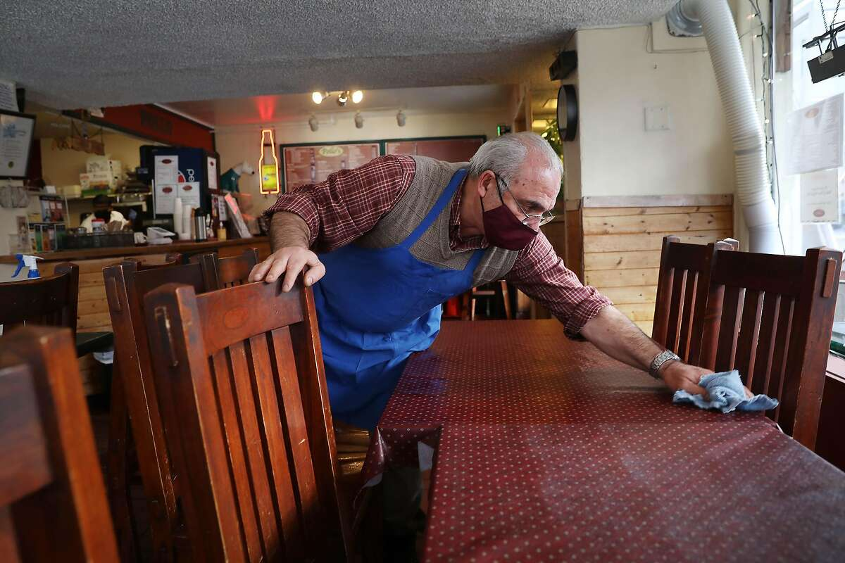 Mostafa Hallaji, owner operator Pollo's, cleans tables and chairs with alcohol as he prepares for re-opening after Alameda County was moved to the red tier on Tuesday, March 9, 2021 in Oakland, Calif.
