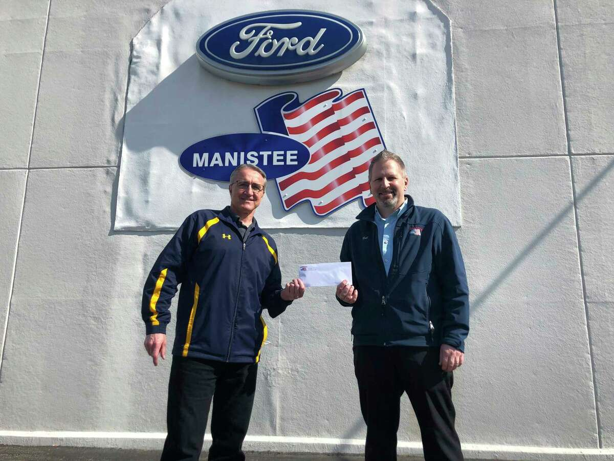 Daryl Pieczynski (left), 350 Club Board Member, receives a donation form Rob Pepera, general manager at Manistee Ford. (Courtesy photo)