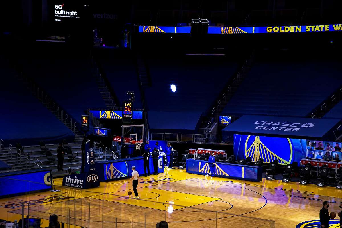 The Golden State Warriors enter the court with less than 12 minutes until tipoff in an NBA game against the Charlotte Hornets at Chase Center, Friday, Feb. 26, 2021, in San Francisco, Calif. The center is not selling tickets to the game, amid the novel coronavirus pandemic.