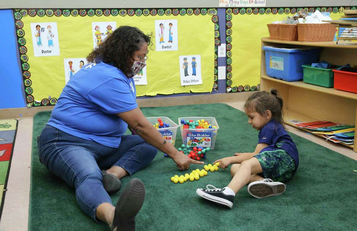 A teacher works with a child at the YMCA Labor Child Care Center in April. Child care centers have been hit hard by the pandemic, but the state now has the opportunity to invest in and transform early learning with federal dollars and state legislative action.