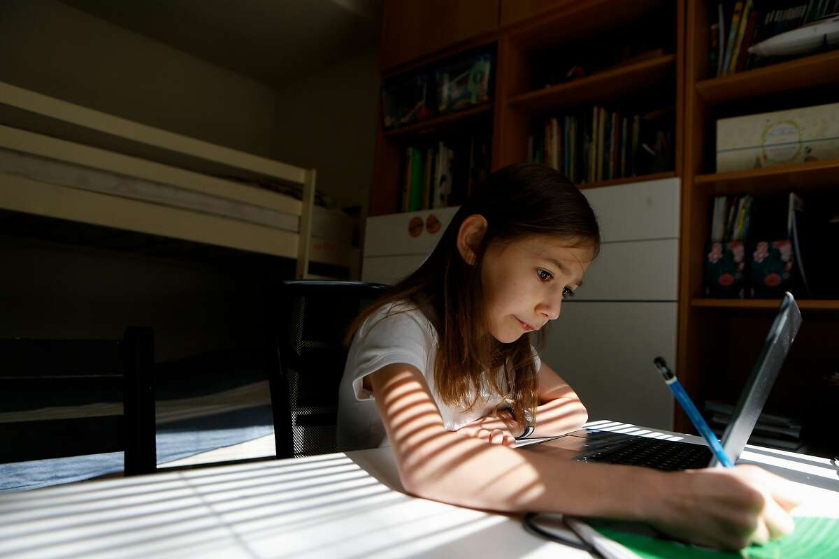 Vardeni Vardanyan, 8, sits at a desk in her bedroom while she attends her 2nd grade Zoom class for Marshall Elementary on Monday, March 8, 2021 in San Francisco, Calif. Vardeni has trouble staying focused during Zoom classes and her school was not on the list of schools reopening at the end of April.
