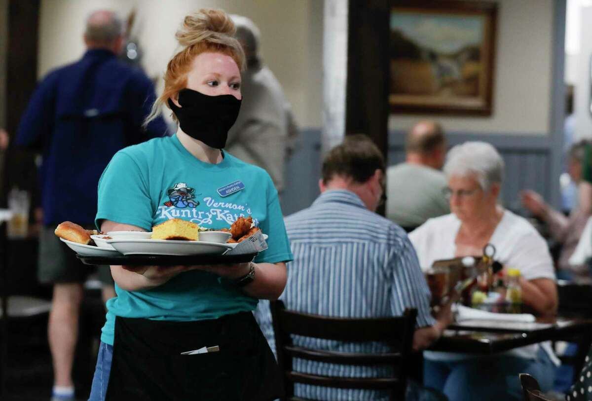 Server Ashden Maybin carries orders to customers at Vernon's Kuntry Katfish, Wednesday, March 10, 2021, in Conroe. Gov. Greg Abbott's mask order was lifted Wednesday and allowed businesses and facilities to open to 100% capacity.