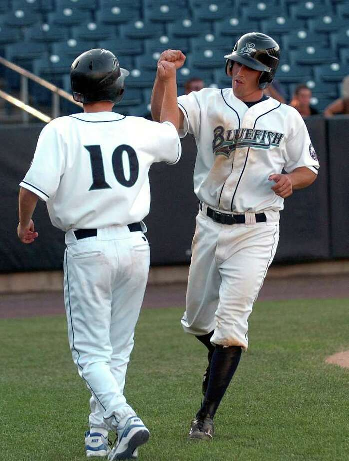 Game action between the Bridgeport Bluefish and Lancaster at the Arena at Harbor Yard in Bridgeport, Conn. on Wednesday September 8, 2010. Bluefish's #5 Adam Greenberg, right, celebrates after bringing in a run. Photo: Christian Abraham / Connecticut Post