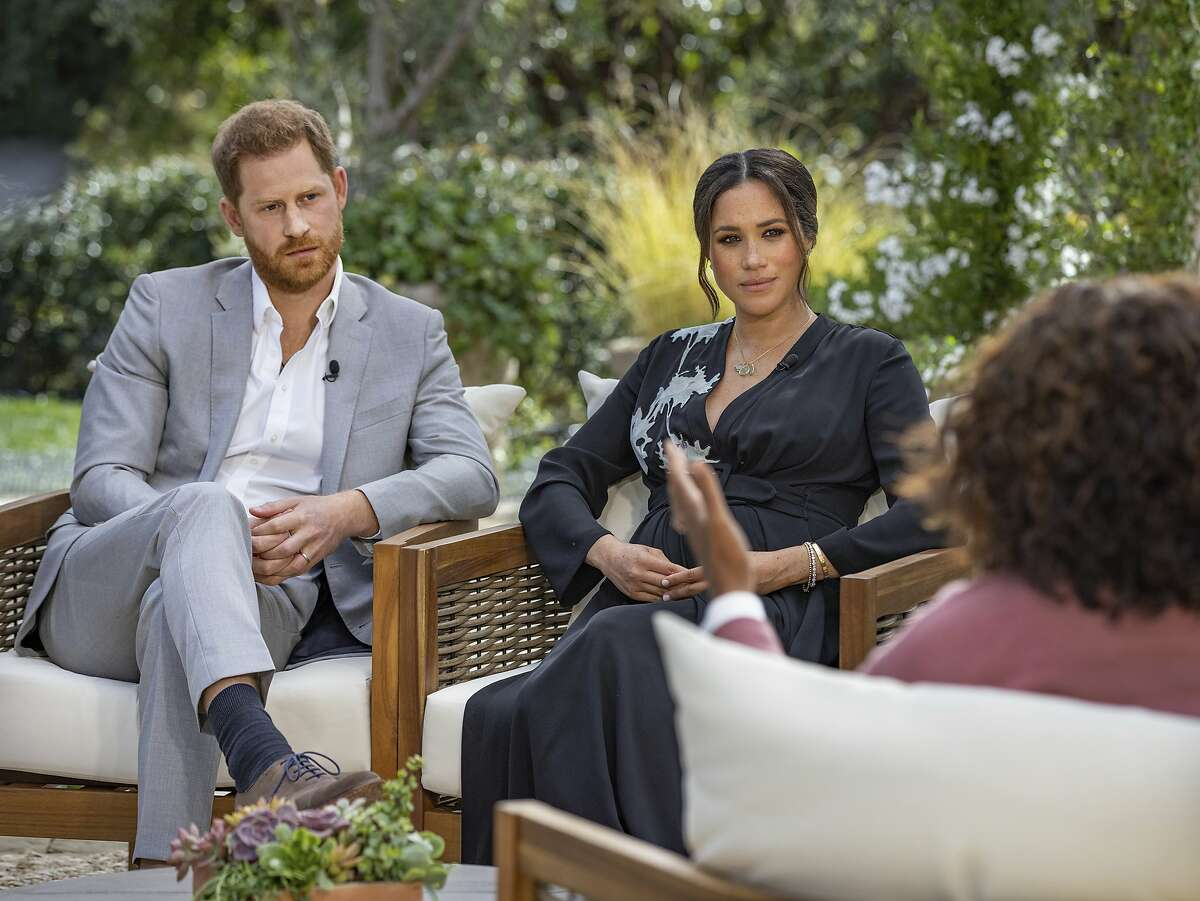 This image provided by Harpo Productions shows Prince Harry, from left, and Meghan, Duchess of Sussex, in conversation with Oprah Winfrey. Almost as soon as the interview aired, many were quick to deny Meghan's allegations of racism on social media. Many say it was painful to watch Meghan's experiences with racism invalidated by the royal family, members of the media and the public, offering up yet another example of a Black woman's experience being disregarded and denied. (Joe Pugliese/Harpo Productions via AP, File)