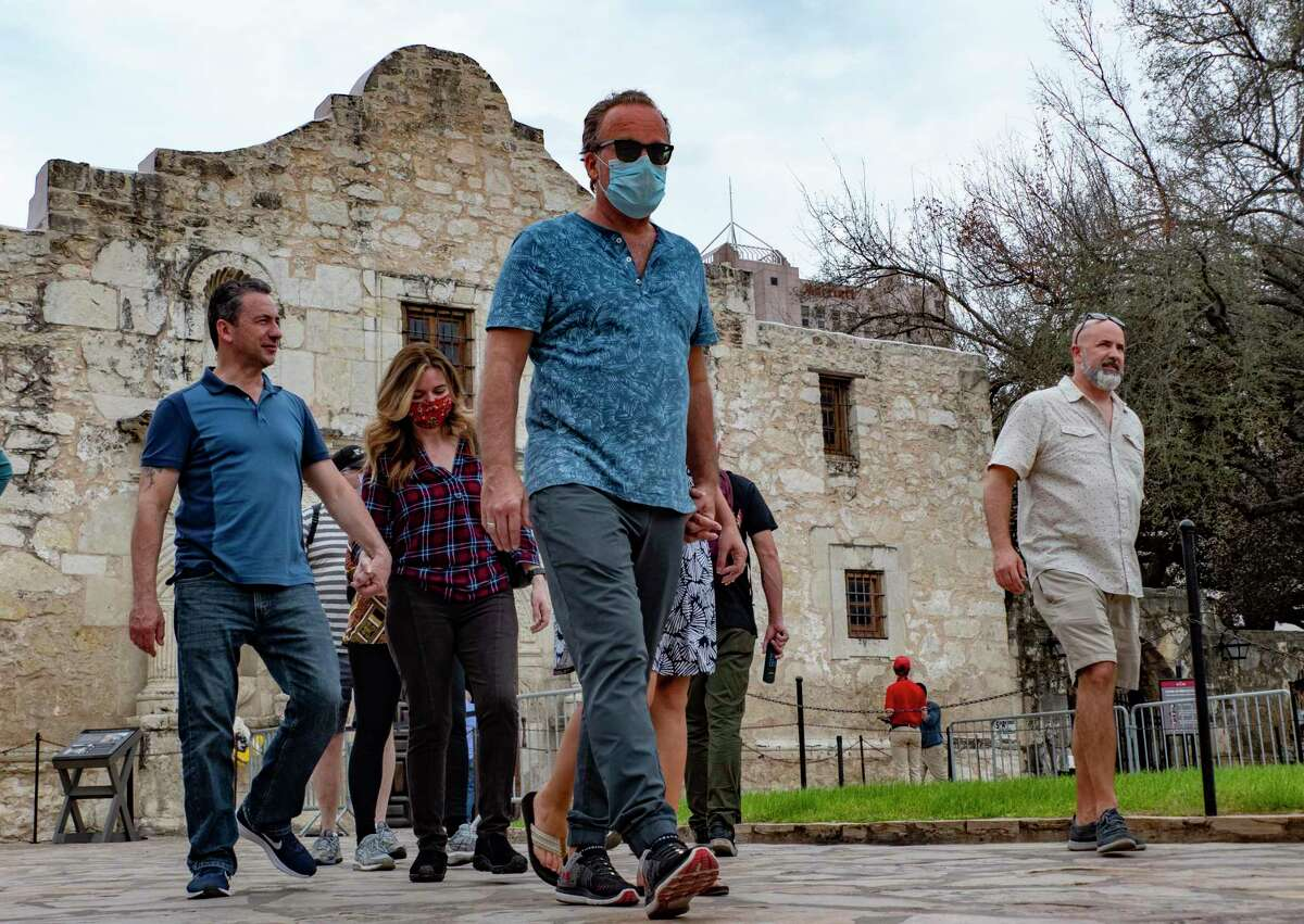Some people were masks and some do not as they tour the Alamo grounds on Wednesday, March 10, 2021. With the state lifting its restrictions on masks and operating capacity, some businesses have opted to keep the precautions that have kept their employees and customers safe throughout the pandemic. Other places are giving customers the option to decide whether or not they will wear a mask.