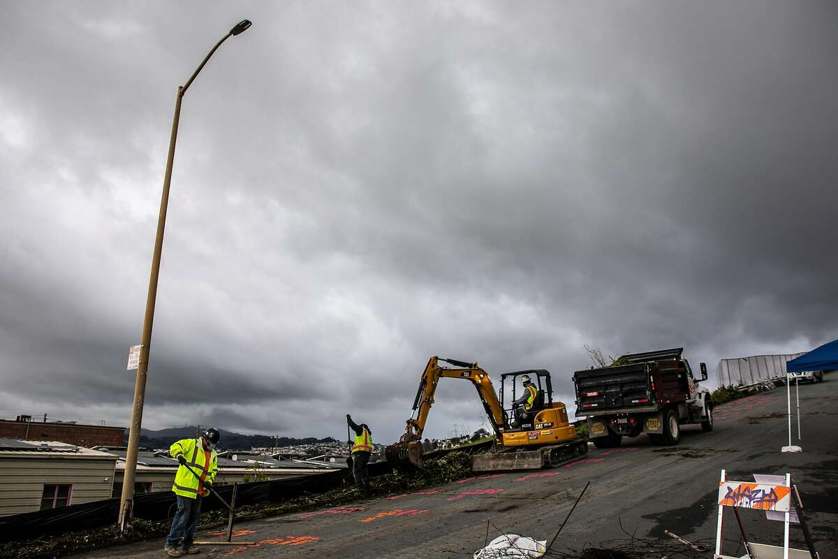 Workers remove vegetation and debris at a construction site on 26th street in the Potrero Annex-Terrace neighborhood.