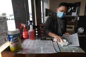 Kobe Trongjittham sanitizes menus at Chaba Thai. The restaurant reopened for in-person dining just a month ago and will continue to require masks to be worn when not seated at a table. Photo made Wednesday, March 10, 2021 Kim Brent/The Enterprise