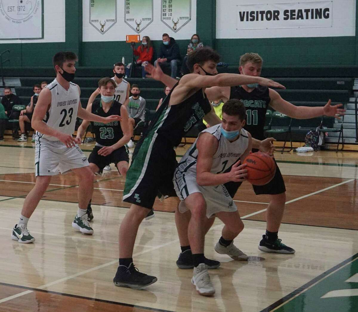 Senior Isaac McKinley, of Pine River, guards the ball whiledouble teamed along the baseline during PR's loss to Houghton Lake on Wednesday night. (Pioneer photo/Joe Judd)