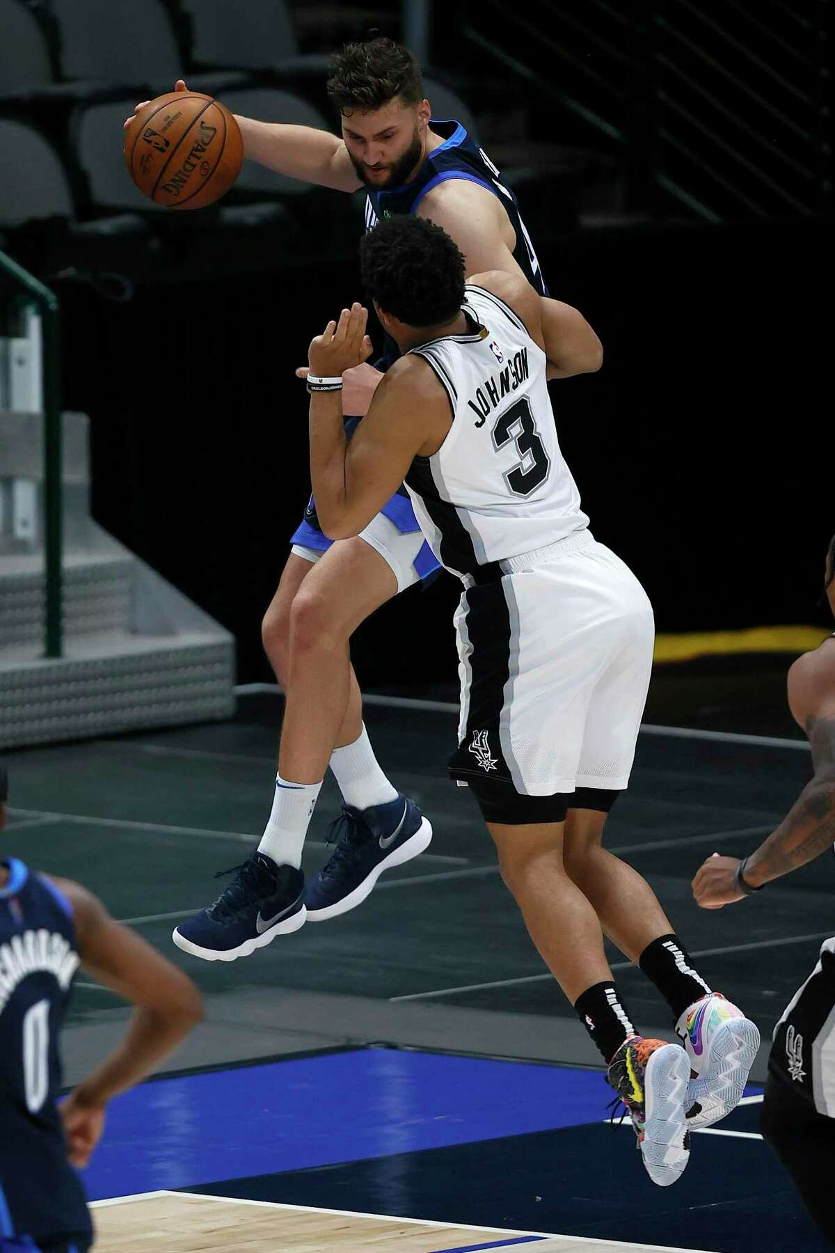 DALLAS, TEXAS - MARCH 10: Maxi Kleber #42 of the Dallas Mavericks scrambles for a loose ball against Keldon Johnson #3 of the San Antonio Spurs in the fourth quarter at American Airlines Center on March 10, 2021 in Dallas, Texas. NOTE TO USER: User expressly acknowledges and agrees that, by downloading and or using this photograph, User is consenting to the terms and conditions of the Getty Images License Agreement. (Photo by Tom Pennington/Getty Images)
