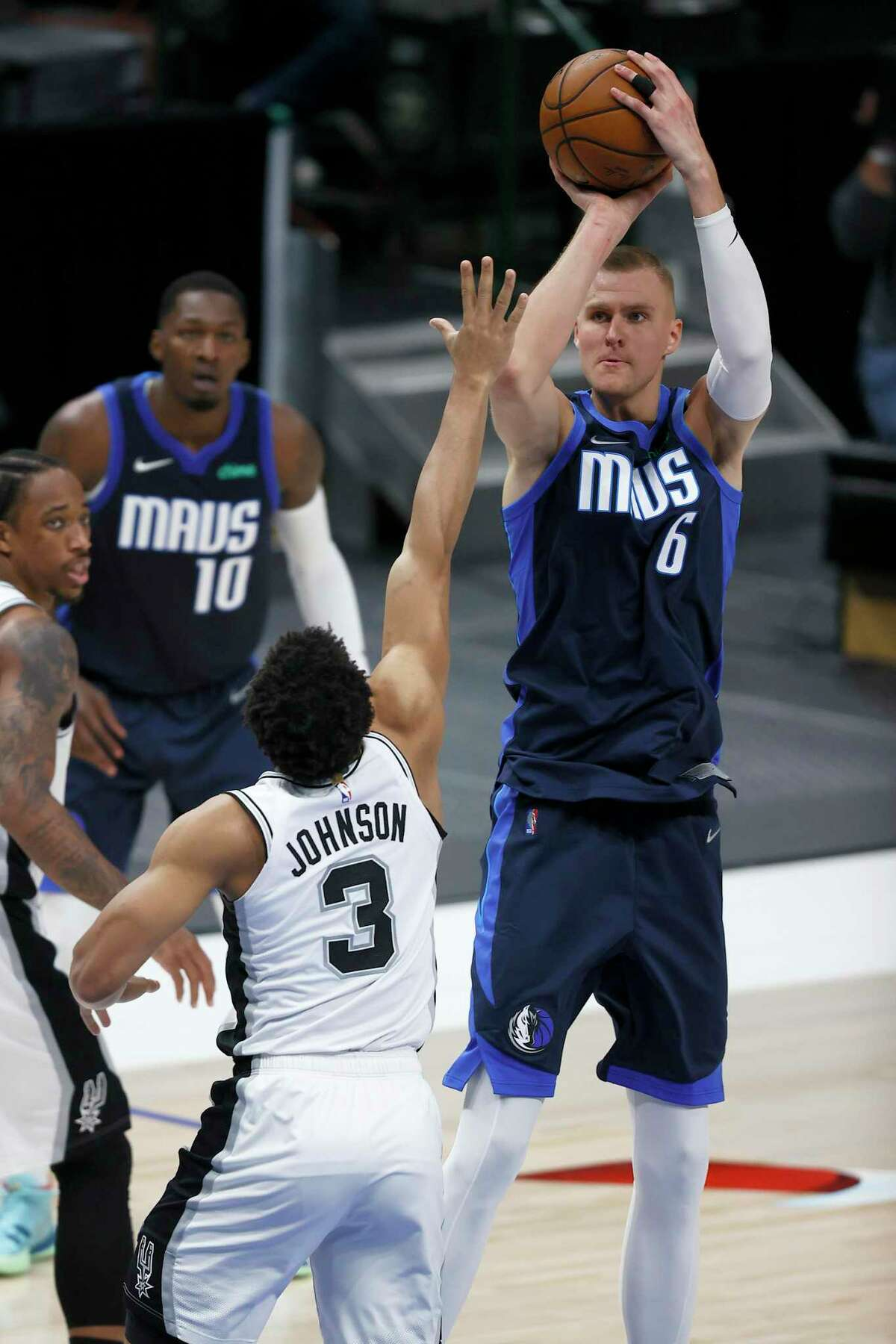 DALLAS, TEXAS - MARCH 10: Kristaps Porzingis #6 of the Dallas Mavericks shoots the ball against Keldon Johnson #3 of the San Antonio Spurs in the fourth quarter at American Airlines Center on March 10, 2021 in Dallas, Texas. NOTE TO USER: User expressly acknowledges and agrees that, by downloading and or using this photograph, User is consenting to the terms and conditions of the Getty Images License Agreement. (Photo by Tom Pennington/Getty Images)