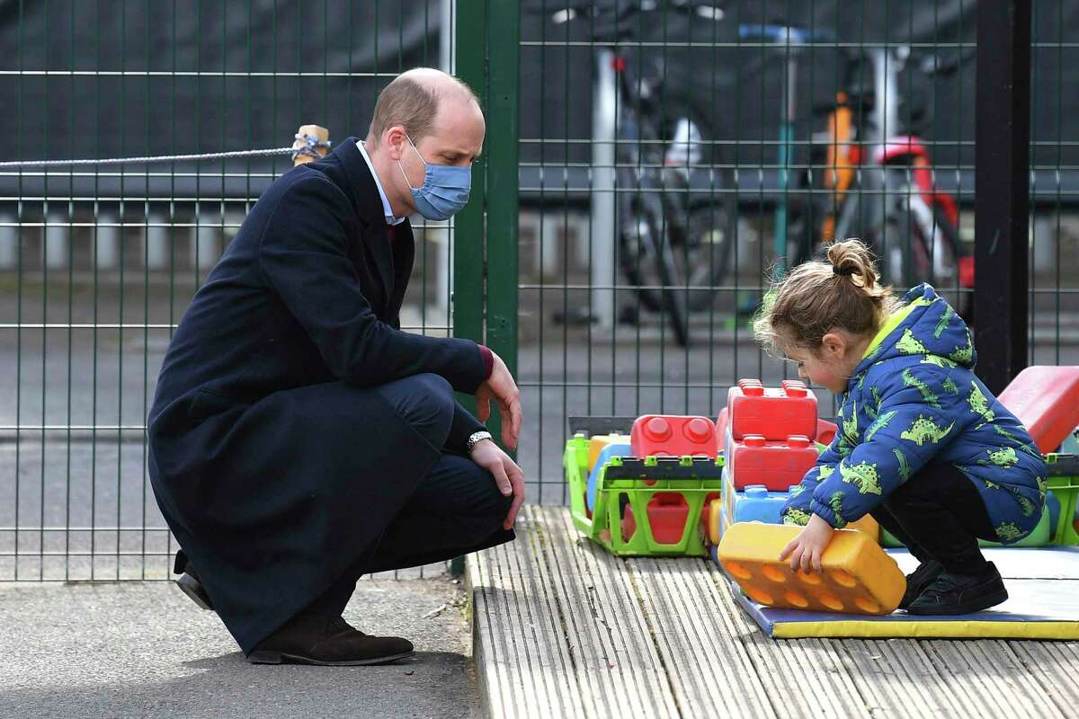 Britain's Prince William watches a child in the playground during a visit with Kate, Duchess of Cambridge to School21, a school in east London, Thursday March 11, 2021. (Justin Tallis/Pool via AP)