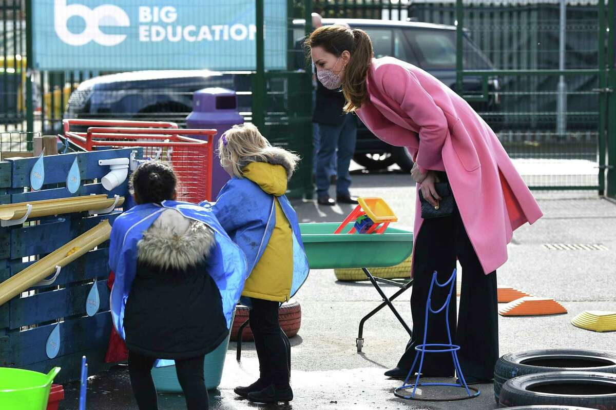 Britain's Kate, Duchess of Cambridge talks with children in the water area of the playground during a visit with Prince William to School21, a school in east London, Thursday March 11, 2021. (Justin Tallis/Pool via AP)