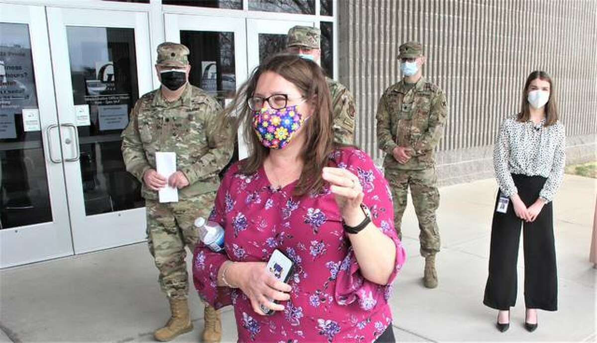"""Amy Yeager, director of community health and public information officer for the Madison County Health Department, speaks during a """"press tour"""" of the county's vaccination center at the Gateway Convention Center in Collinsville. Behind her are officials from the Illinois National Guard and Madison County Health Department. Since the arrival of the Guard about two weeks ago, the Health Department has been able to dramatically improve the number of people it can vaccinate."""