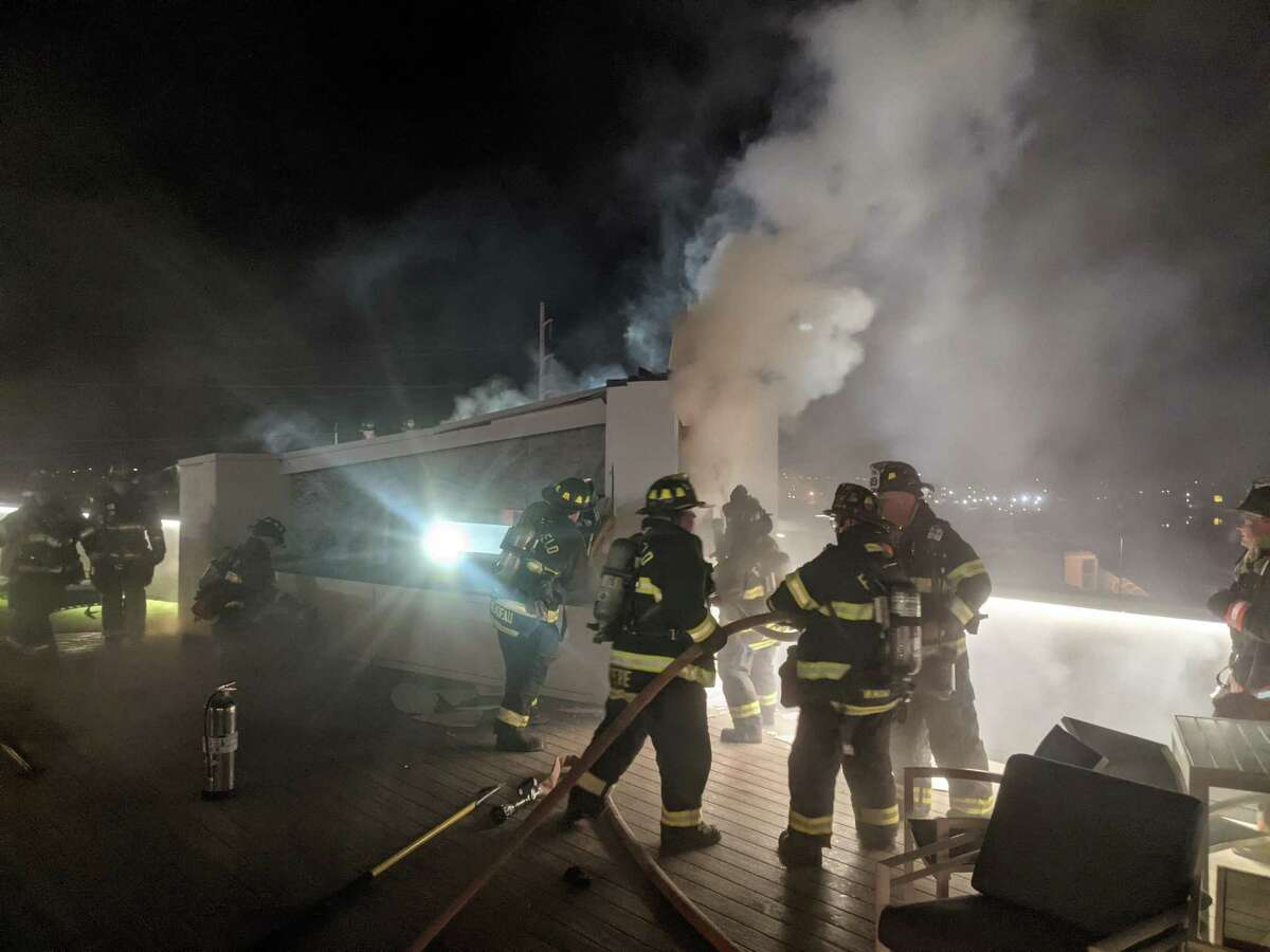 Firefighters operating at a fire on the rooftop deck of the Alto Fairfield Metro Complex on Kings Highway in Fairfield, Conn., on March 10, 2021.