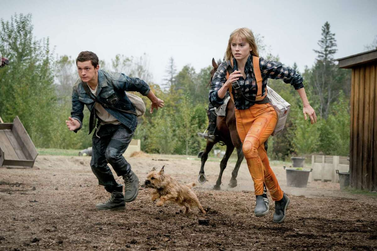 """Daisy Ridley, Manchee the dog and Tom Holland in the movie """"Chaos Walking."""" (Murray Close/Lionsgate)"""