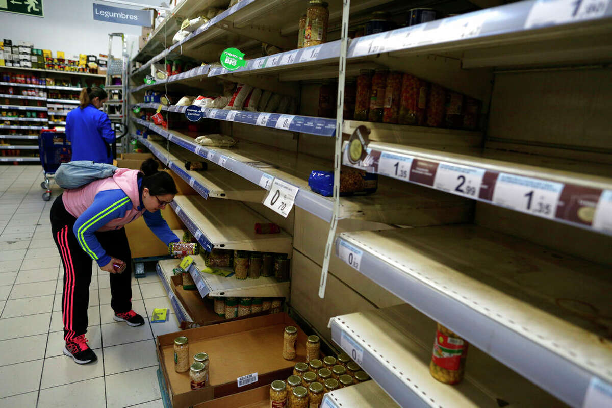 A shopper holds an item surrounded by mostly empty shelves in a supermarket in Madrid, Spain, Tuesday, March 10, 2020. People have emptied shelves of food and supplies in supermarkets in Madrid after Spain's health minister on Monday announced a sharp spike in coronavirus cases in and around the national capital. (AP Photo/Manu Fernandez)