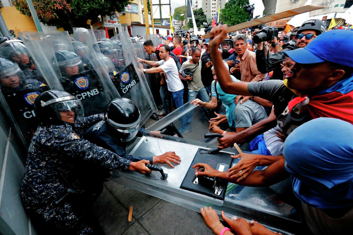 Opposition protesters clash with police blocking their march in Caracas, Venezuela, Tuesday, March 10, 2020. U.S.-backed Venezuelan political leader Juan Guaido is leading a march aimed at retaking the National Assembly legislative building, which opposition lawmakers have been blocked from entering. (AP Photo/Ariana Cubillos)