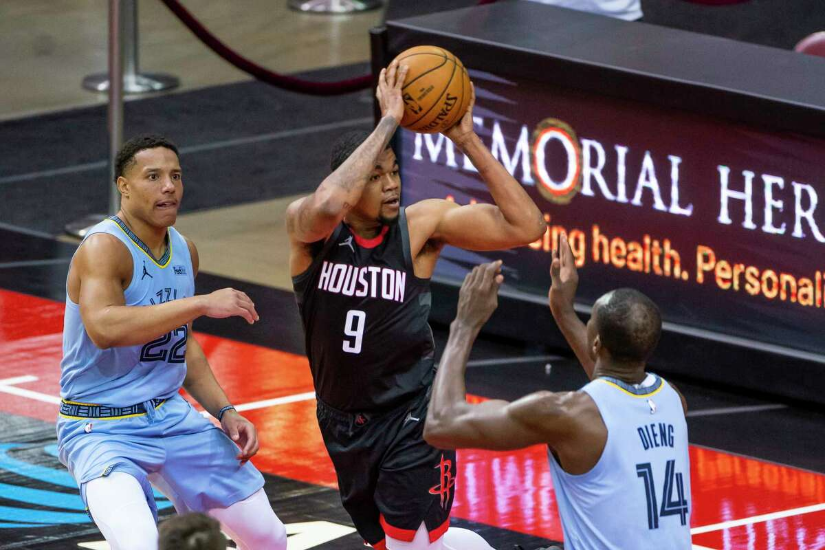 Houston Rockets guard Mason Jones (9) passes over Memphis Grizzlies center Gorgui Dieng (14) during the fourth quarter of an NBA basketball game between the Houston Rockets and Memphis Grizzlies on Sunday, Feb. 28, 2021, at Toyota Center in Houston.