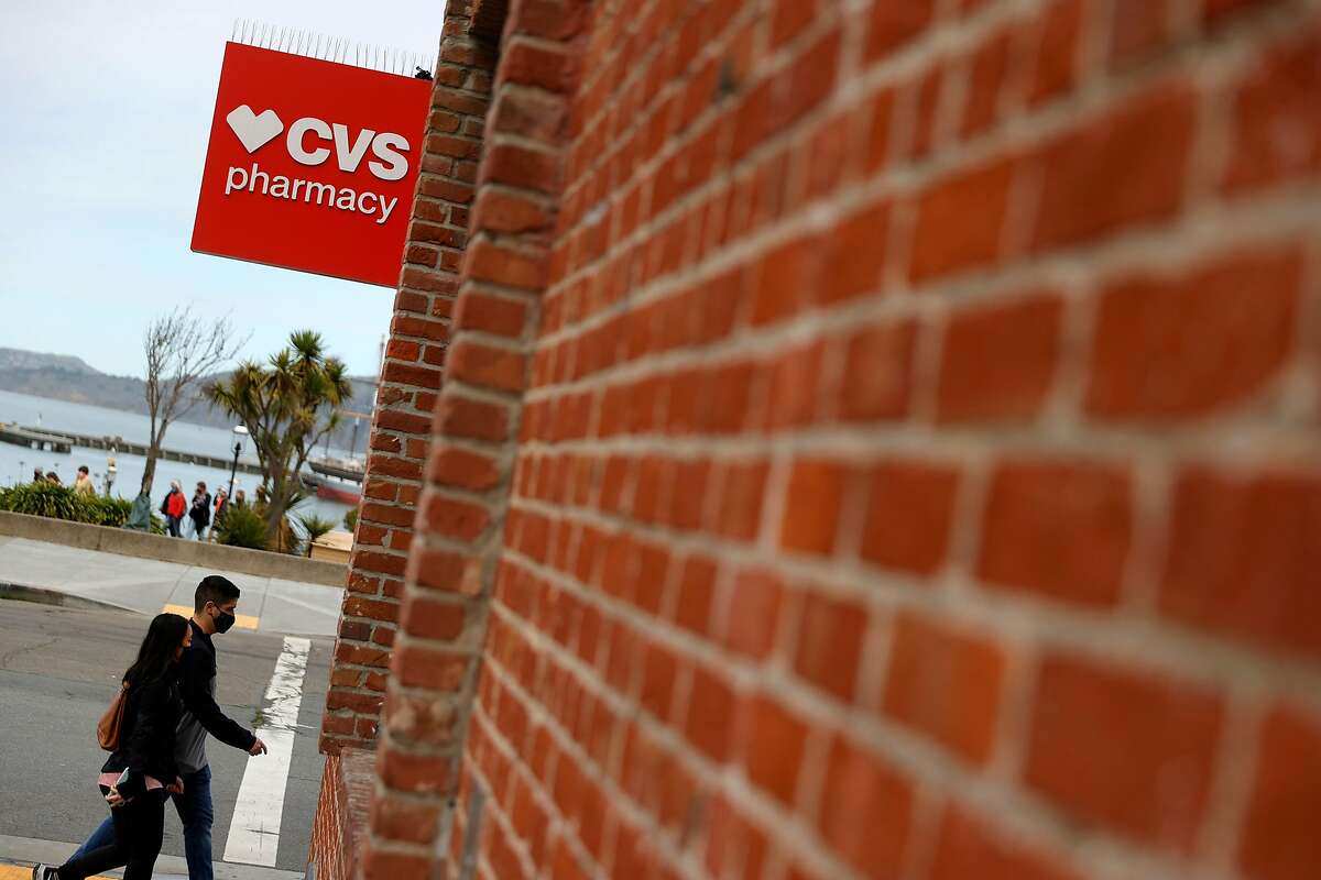 Pedestrians walk by a CVS store on February 16, 2021 in San Francisco, California. The retailer announced it will begin administering the coronavirus vaccine at 119 additional pharmacy locations in California, including in five Bay Area counties, beginning Sunday.