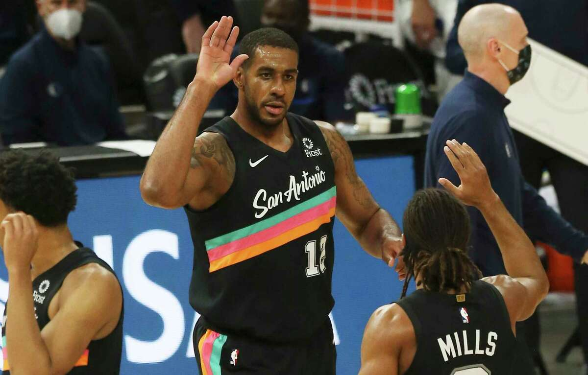 Spurs' LaMarcus Aldridge (12) gets a high-five from Patty Mills (08) after hitting a pair of threes against the Dallas Mavericks at the AT&T Center on Friday, Jan. 22, 2021.