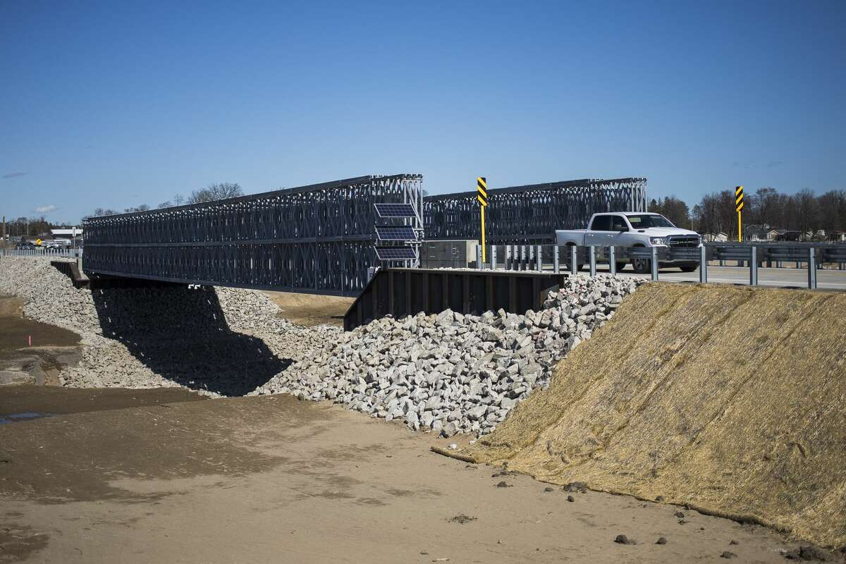 Drivers cross a 230-foot temporary prefabricated steel bridge over the Tobacco River after it was officially opened by the Michigan Department of Transportation (MDOT) Thursday, March 11, 2021 in Edenville. (Katy Kildee/kkildee@mdn.net)