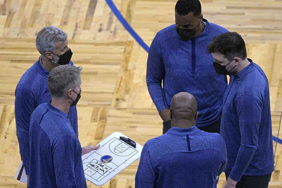 Golden State Warriors head coach Steve Kerr holds a clipboard while talking with members of his coaching staff during a timeout in the first half of an NBA basketball game against the Orlando Magic, Friday, Feb. 19, 2021, in Orlando, Fla. (AP Photo/Phelan M. Ebenhack)