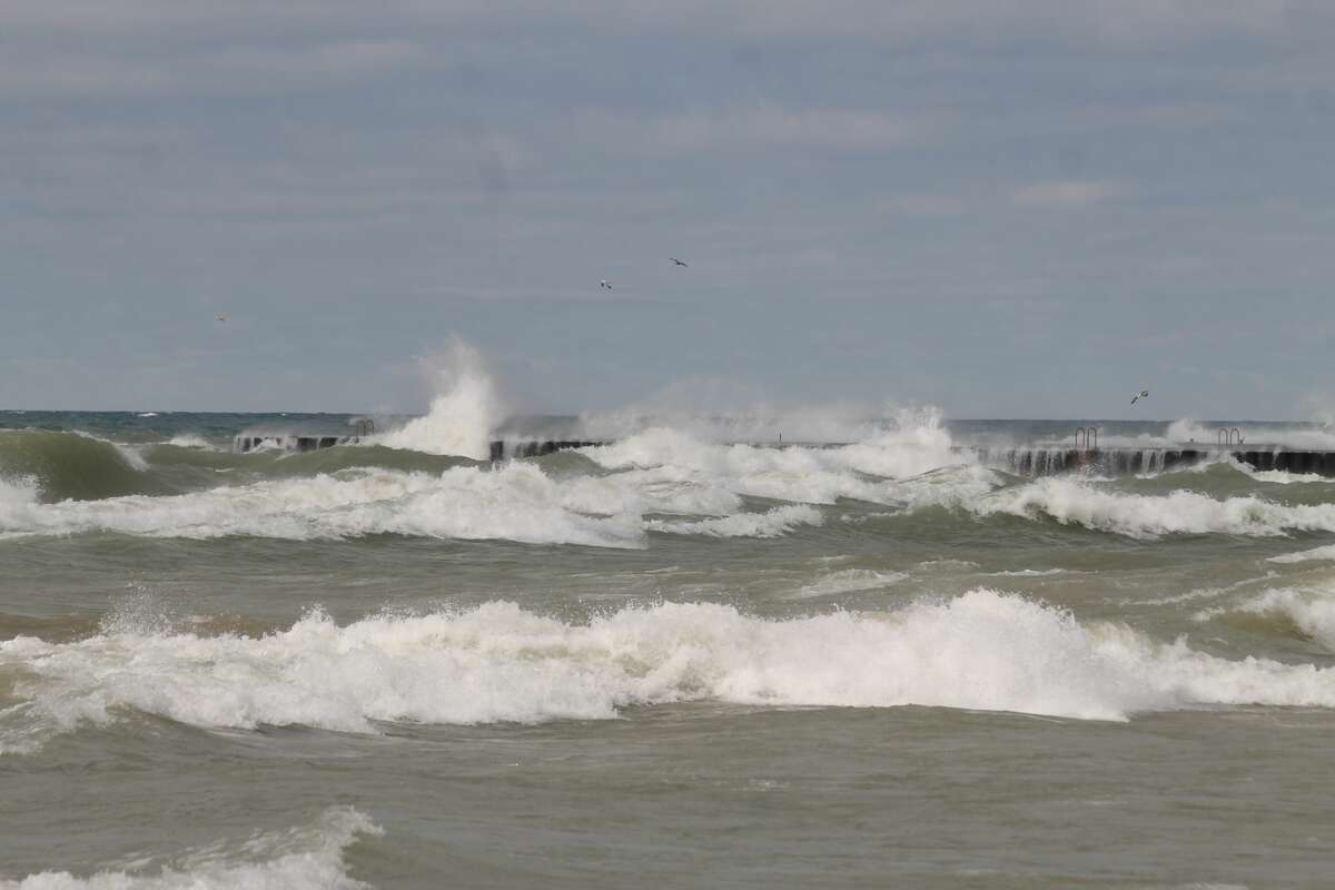 Waves crash over First Street Pier in Manistee on Thursday.